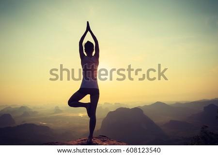 young fitness woman meditating on sunrise mountain peak #608123540