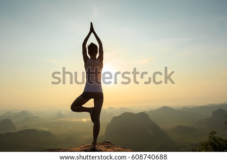 young fitness woman meditating on sunrise mountain peak #608740688