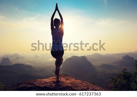 young fitness woman meditating on sunrise mountain peak #617237363
