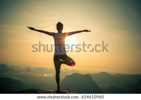 young fitness woman meditating on sunrise mountain peak