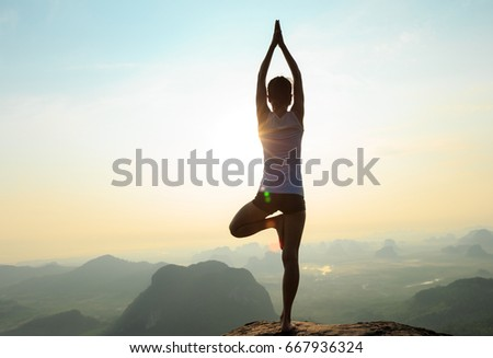 young fitness woman meditating on sunrise mountain peak #667936324