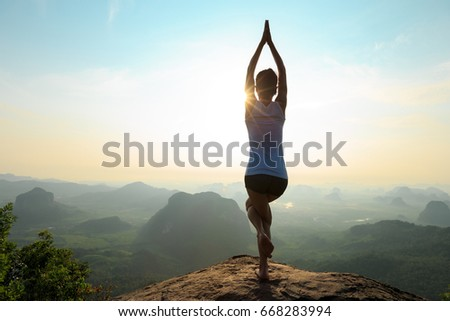 young fitness woman meditating on sunrise mountain peak #668283994