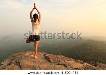 young fitness woman practice yoga at mountain peak cliff #415024261