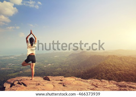young fitness woman practice yoga at mountain peak cliff #466373939