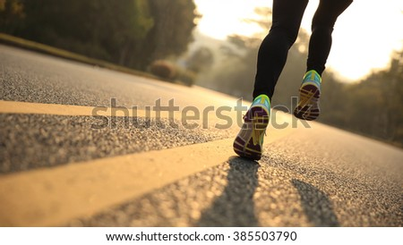 young fitness woman runner athlete legs running at road #385503790
