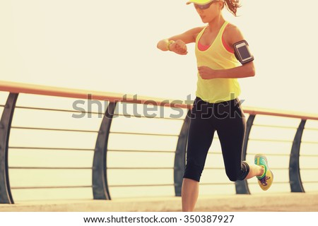 young fitness woman runner checking her running time from smart watch at seaside