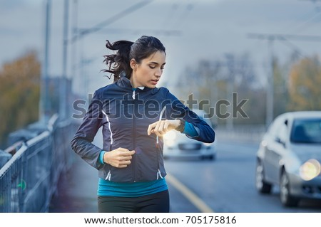 Young fitness woman runner checking time from smart watch. Young woman checking heart rate while jogging on street at dusk. Young woman looking on smartwatch her heartbeat while running in city.