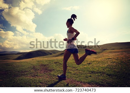 young fitness woman runner running on grassland trail #723740473