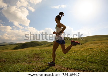 young fitness woman runner running on grassland trail #724109917
