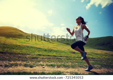 young fitness woman runner running on grassland trail #725345053