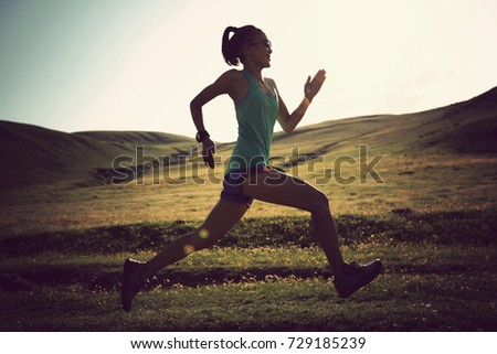 young fitness woman runner running on grassland trail #729185239