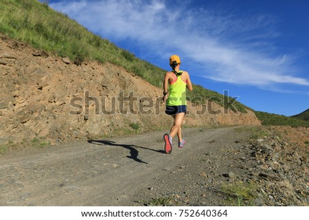 young fitness woman runner running on mountain trail #752640364