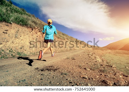 young fitness woman runner running on mountain trail #752641000
