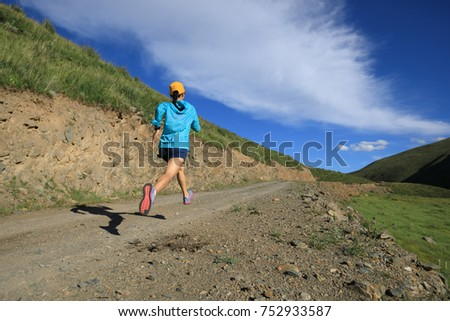 young fitness woman runner running on mountain trail #752933587