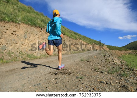 young fitness woman runner running on mountain trail #752935375