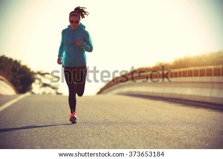 young fitness woman runner running on sunrise road #373653184
