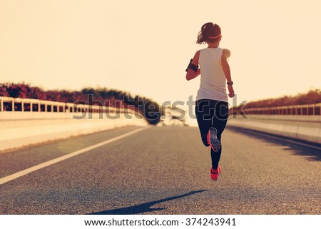 young fitness woman runner running on sunrise road #374243941