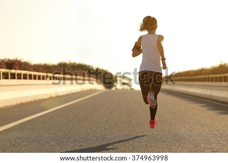 young fitness woman runner running on sunrise road #374963998