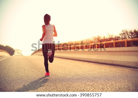young fitness woman runner running on sunrise road #390855757