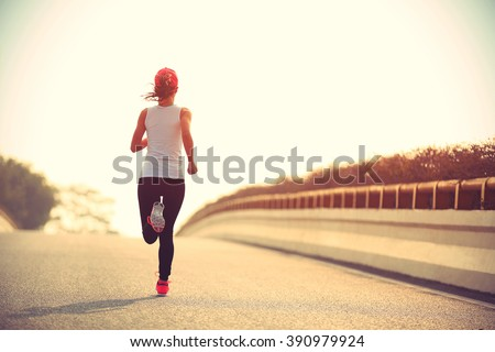 young fitness woman runner running on sunrise road #390979924