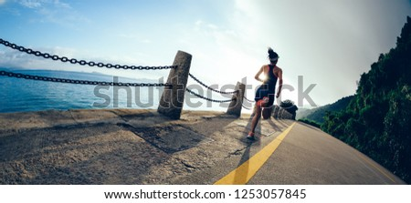 young fitness woman runner running on sunrise seaside road #1253057845