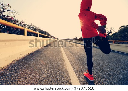 young fitness woman runner stretching legs before run Stock photo ©