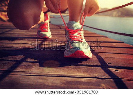 young fitness woman runner tying shoelace at seaside boardwalk
