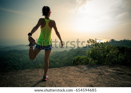 Young fitness woman runner warming up at tropical mountain peak