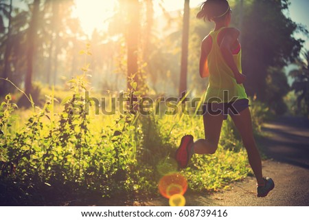 Photo of  Young fitness woman running at morning tropical forest trail