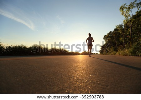 young fitness woman running on sunrise seaside trail #352503788
