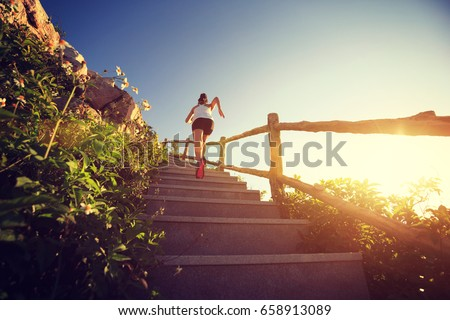 young fitness woman running upstairs on mountain stairs #658913089