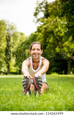 Young fitness woman stretching muscles before sport activity - outdoor in park
