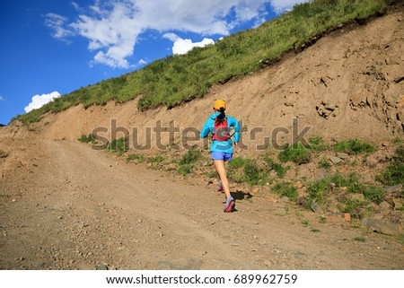 young fitness woman trail runner running in the nature #689962759