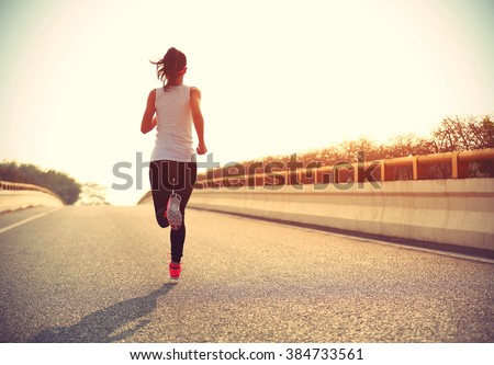 young fitness woman trail runner running  on city road