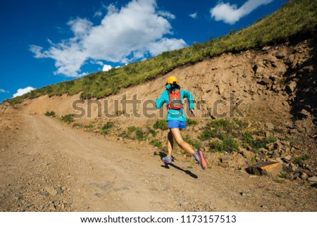 Young fitness woman trail runner running on hill    #1173157513