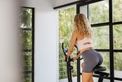 Young fitness Woman use exercise bike and training hard at home gym near window with nature view. Sporty lifestyle