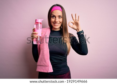 Young fitness woman wearing sport clothes and towel drinking water from take away bottle doing ok sign with fingers, excellent symbol Foto stock ©