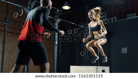 Young fitness woman with man crossfit workouts Sporty fit girl doing exercises with the help of a personal trainer in a modern gym Male trainer helping woman on her workout routines
