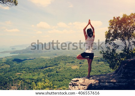 young fitness yoga woman at mountain peak #406557616