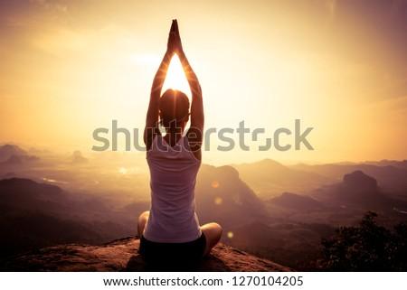 young fitness yoga woman meditating on sunrise mountain peak #1270104205