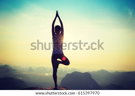 young fitness yoga woman meditating on sunrise mountain peak #615397970