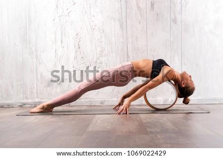 Young flexible woman doing purvottanasana yoga pose with wheel