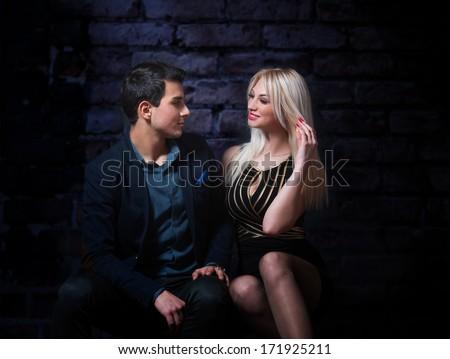 Young flirting couple, dark background