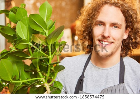 Young florist delivering a green plant as customer service