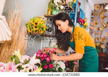 Young florist examining flowers at the shop