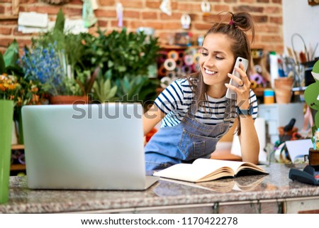 Young florist looking at laptop and answering phone call while leaning on counter in the shop