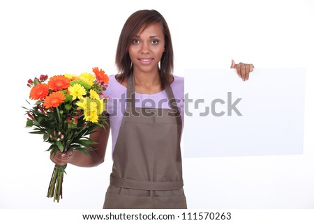 Young florist with bouquet and white card