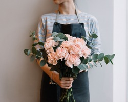 Young florist woman holding freshly made minimalistic blossoming flower bouquet of pastel pink carnations and eucalyptus on the grey wall background.