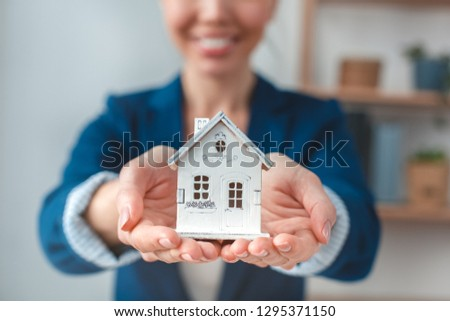 Young fmale agent at real estate agency sitting at table holding house model close-up smiling joyful blurred background