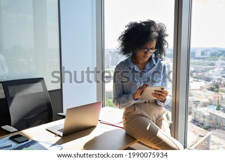 Young focused African American businesswoman sitting on desk holding using tablet computer device in modern office in high floor building with panoramic urban capital city view.